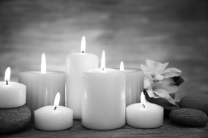 black and white photo of white candles burning