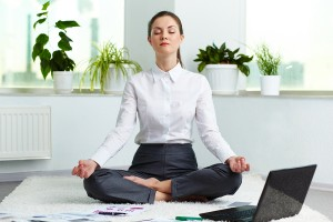 Portrait of attractive white collar worker meditating in office