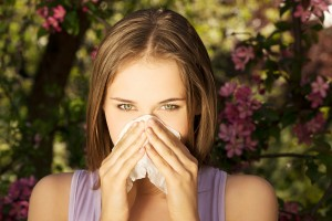young woman standing near trees with allergy