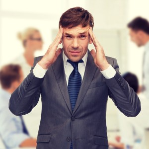 stressed businessman holding head